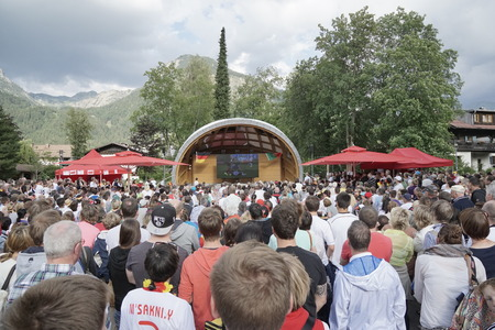 jubilate: OBERSTDORF GERMANY JUNE 16: Spectators of the 2014 Soccer World cup in Brazil  celebrating the game between Germany and Portugal at the famous winter sports resort Oberstdorf with its picturesque mountains in the background
