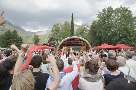 jubilating: OBERSTDORF GERMANY JUNE 16: Spectators of the 2014 Soccer World cup in Brazil  celebrating the game between Germany and Portugal at the famous winter sports resort Oberstdorf with its picturesque mountains in the background