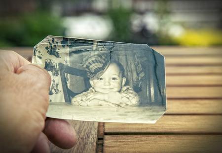 El hombre sostiene una imagen de la infancia de los años sesenta en la mano viñeteado Fuerte y bordes borrosos para aumentar el efecto de memoria Foto de archivo