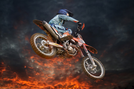 Jumping motocross rider with firestorm in the background and red glowing spinning rear wheel