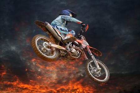 Saltando piloto de motocross con tormenta de fuego en el fondo y el rojo brillante de girar la rueda trasera Foto de archivo