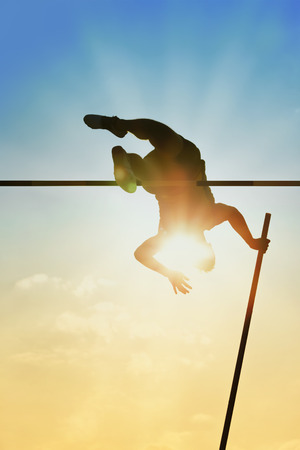 Pole vault over the bar with  back light photo