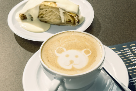 specialty: Cappuccino with little bear decoration drawn into the foam. In the background the austrian specialty \Apfelstrudel\ with vanilla sauce.
