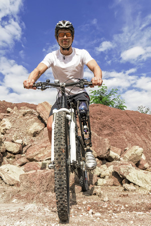 limp: Shot of young male mountain bike rider with leg prosthesis between rocks.