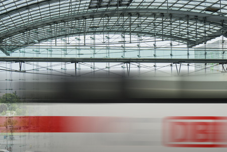 db: BERLIN, GERMANY- AUGUST 10, 2013: Passing ICE train with brand of the Deutsche Bahn at the main train station of Berlin, Hauptbahnhof