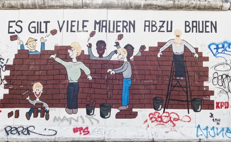 BERLIN - AUGUST 24, 2014 : The East Side Gallery is the largest outdoor art gallery in the world.This piece of the wall shows a graffiti of an unknown artist , in which multiethnic people  remove bricks of the wall.
