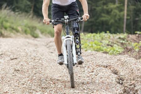 Mountain bike rider with leg prosthesis rides a gravel track
