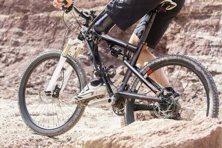 Shot of mountain bike rider with leg prosthesis between rocks.