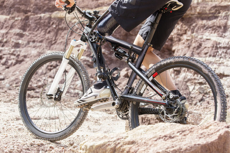 amputation: Shot of mountain bike rider with leg prosthesis between rocks.