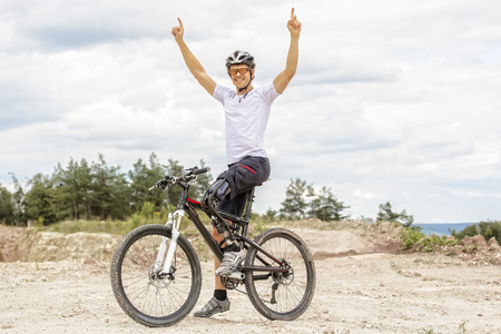 limp: Shot of young  mountain bike rider with leg prosthesis raising up his arms