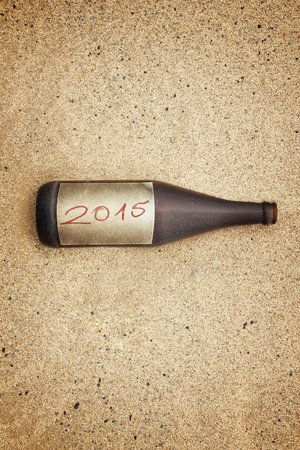 washed out: Vintage version of washed out bottle with 2015  label on gravel beach.