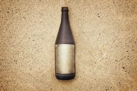 washed out: Vintage version of washed out bottle with empty label on gravel beach.