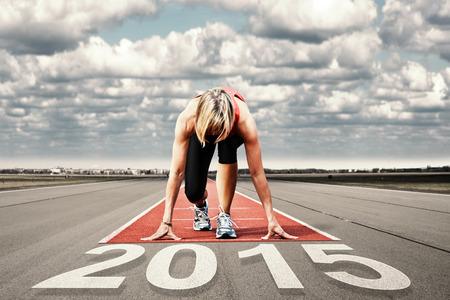 Weibliche Sprinter warten auf den Start auf einem Flughafen runway.In Vordergrund perspektivische Ansicht der Zeitpunkt 2015.