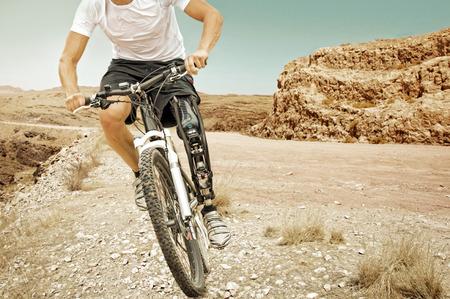 Gehandicapte mountainbike ruiter rijdt in een dorre landschap