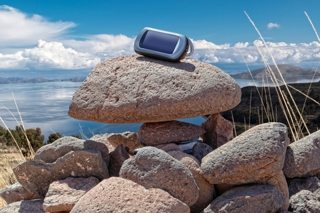 Gps device is placed on stacked rocks of geochache hide. photo