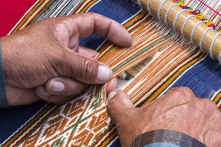 loom: Peruan weaver weaves traditional peruan carpet Stock Photo