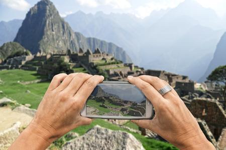 south  america: Fotógrafo de sexo femenino con el teléfono inteligente toma una fotografía de las ruinas de Machu Picchu Foto de archivo