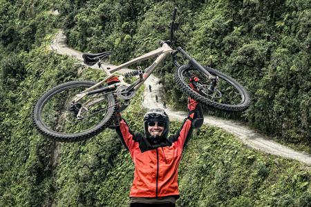 Mountain biker pulls up his mountain bike at the famous downhill trail Road of death in Bolivia. In the background there are mountain biker riding the track. Stock Photo