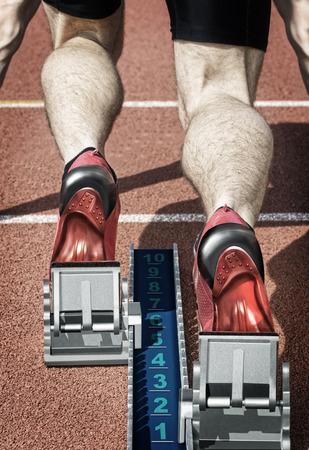 vogelspuren: Draufsicht auf einen männlichen kurzen Strecke Läufer in den Blöcken. Verblassenden Farben und hart mit eigenen Design Ersetzte Laufschuhe und Startblock unterstreichen die Wirkung Abbildung des Fotos.