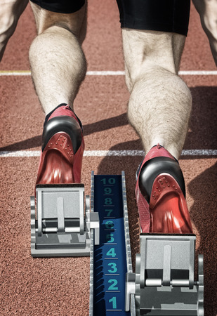 start position: Top view of a male short track runner in the blocks. Desaturated colors and hard with own design Replaced running shoes and startblock are underlining the illustration effect of the photo. Stock Photo