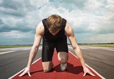 Männliche Version von Flughafenlandebahn Starter. Runner in Startposition kniet mit gesenktem Kopf auf einem roten Tartanoberfläche, bereit, zu nehmen.