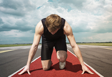 race start: Male version of airport runway starter. Runner in start position kneels with lowered head on a red tartan surface, ready to take of.