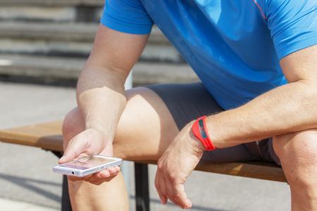 fitness: Uomo allegro che si siede su una panchina e controlla i suoi risultati di fitness su uno smartphone. Indossa una vasca inseguitore braccialetto sul braccio sinistro.
