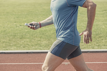 runs: Runner in a stadium checks his fitness results on a smartphone while running. He wears a fitness tracker wristband on the right arm. Photo is filtered with slight antique effect. Stock Photo