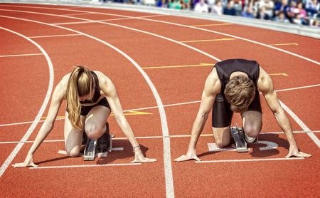 athletics track: Track and field photo of a sprinter couple kneeling in start position ready to start in a curve of a stadium. Blurred spectators surrounding the scene in the background. Guidelines of the tartan track Which are running out the upper left corner of the pic Stock Photo
