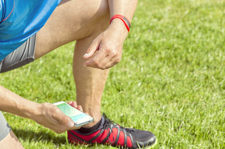 Sportive man kneels on a lawn and checks his fitness results on a smartphone. He wears a fitness tracker wristband on his left arm.