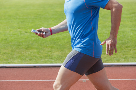 Runner checks his fitness data on a smartphone while running before uploading it to the cloud. He wears a fitness tracker wristband on the right arm. Unfiltered version Stock Photo