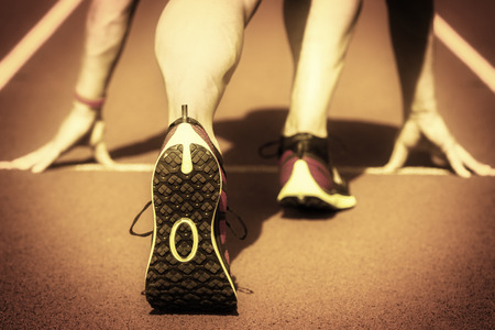 Läufer in einem Stadion ist in Startposition mit den Händen auf der Linie wie ein alter Film interpretiert. Lizenzfreie Bilder