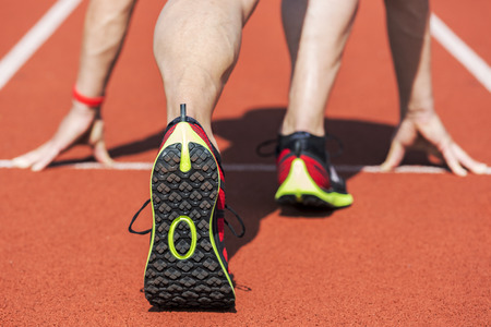 Runner in a stadium is in start position with hands on the line. Unfiltered version. Stock Photo