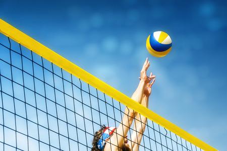 Beachvolley 볼 선수는 그물에 점프 블록에 공을하려고합니다 스톡 콘텐츠