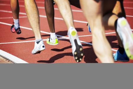 athletics track: Runner legs in a stadium. Focus is on runner with dark skin. Stock Photo