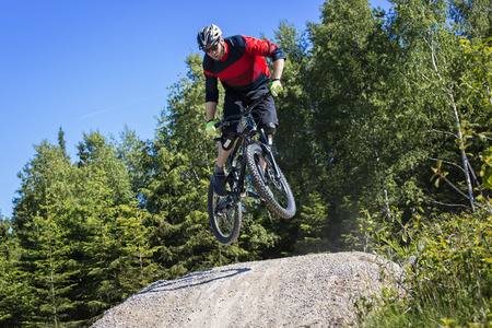 Mountain bike rider jumps over a dirt track kicker Banque d'images