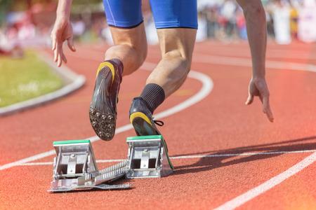 atletismo: Sprinter comienza de los bloques. Filtrado versión con fugas de luz y efecto HDR.