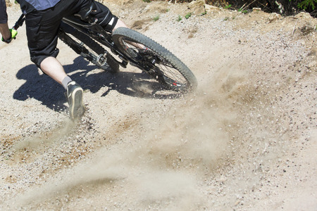 cycler: Unfiltered version of mountain bike rider drifting through a gravity slope of an artificial downhill track. Gravel sprays upwards.