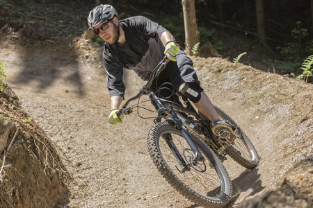 bike trail: Mountain bike rider rides through a gravity slope of an artificial dirt track. The scene is held in earthy colors.