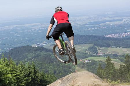진흙 트랙 키커 위로 점프하는 산악 자전거 라이더의 후면보기. 선택된 관점은 절벽으로 점프 한 느낌을줍니다. 배경은 독일에서 검은 숲을 보여줍니