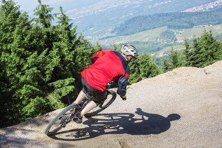 dynamic trend: Mountain bike rider rides through a gravity slope of an artificial dirt track. The background shows the black forest in Germany.