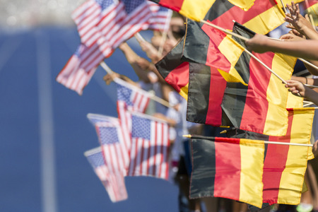 to beckon: Spectators waving with flags of Germany and USA in front of a blue tartan track. Focus is on the german flags in the foreground