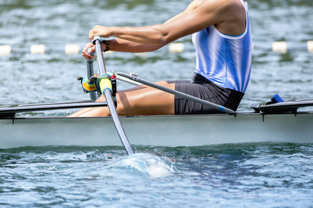 Single rower in a boat strokes the paddle. Stock Photo
