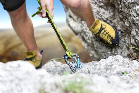登山家は、山の頂上に達する。焦点はロープとカラビナ