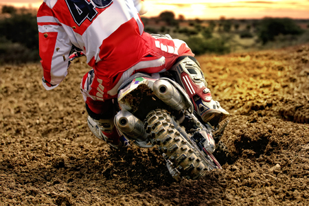 Rear view of drifting motocross bike rider at sundown. The rear wheel is digging  deep in the sand and throws dirt in the air.