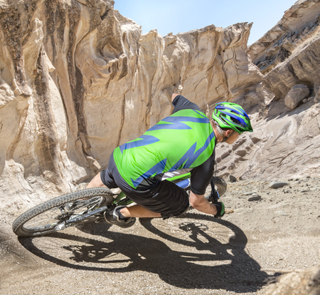 mountain biker: Mountain biker rides a gravity slope track in  a canyon.