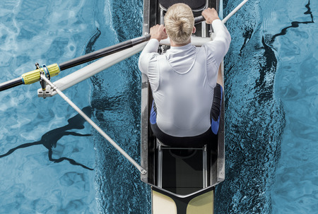 Top view of athletic competition rower, who strokes his  paddle through metallic blue water.