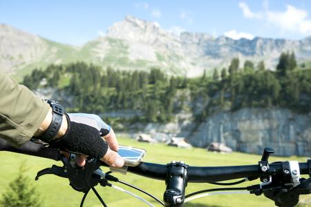 navegacion: Jinete de la bicicleta usa su teléfono inteligente para navegar en los Alpes