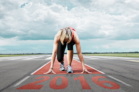 start position: Female runner waits for the start on an airport runway. In the foreground perspective view of the  date 2016.
