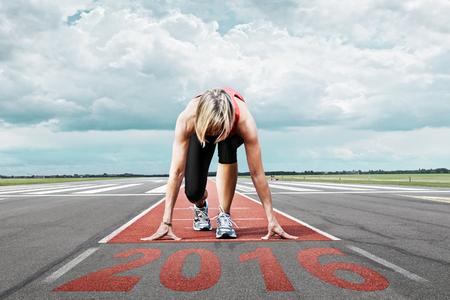 Weiblicher Läufer wartet auf den Start auf einer Landebahn des Flughafens. Im Vordergrund perspektivische Ansicht der Zeitpunkt 2016.